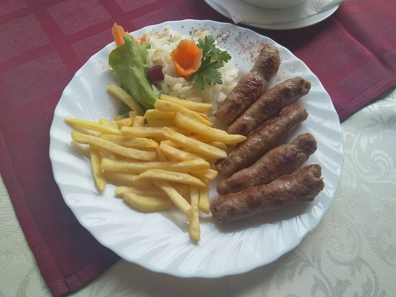 Serbian Ćevapi Served with Chips and Salad