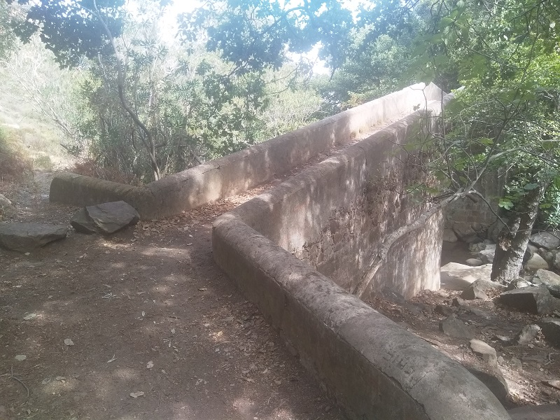 You'll have to cross this old, stone bridge if you walk the Sendero Rio de la Miel