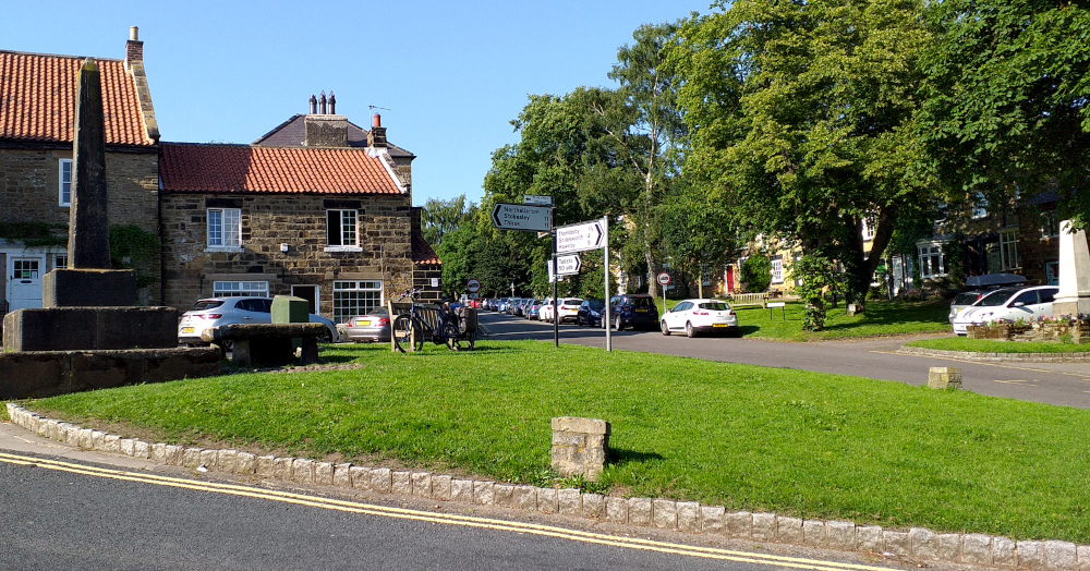 Picture of Osmotherley village green, showing the village cross and stone table (July 2021)